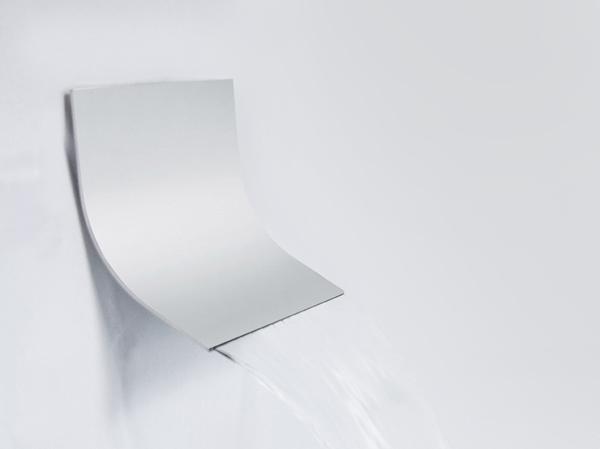Nell'immagine, il soffione Slide, la nuova elegante cascata a muro curva ultrasottile ideata dal centro ricerche FIMA Carlo Frattini nella versione con installazione con braccio a soffitto.